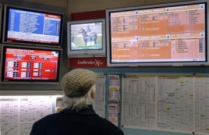 A man watches television screens in a Ladbrokes bookmaker in London